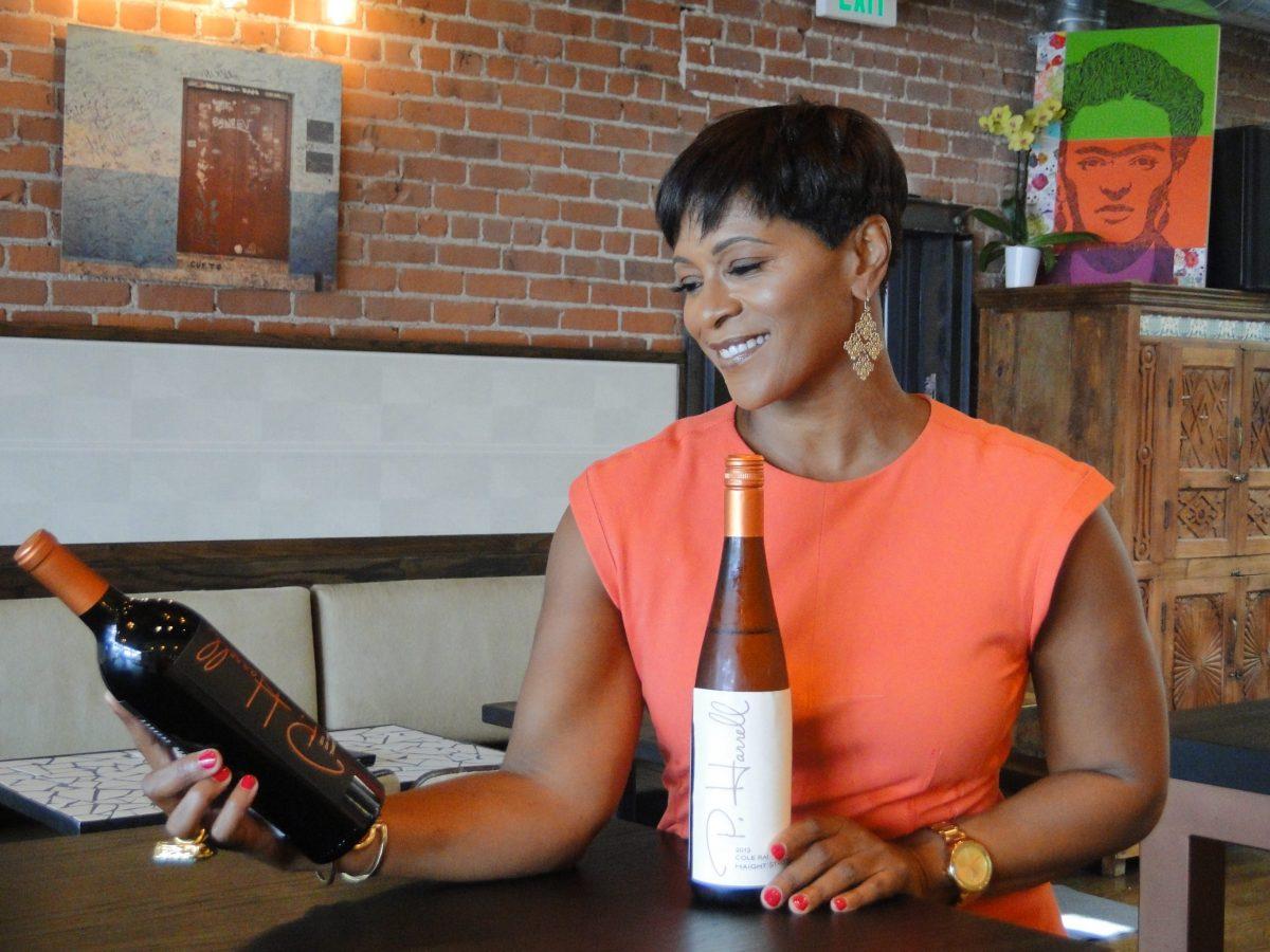 Winemaker Paula Harrell holding bottles of her wine