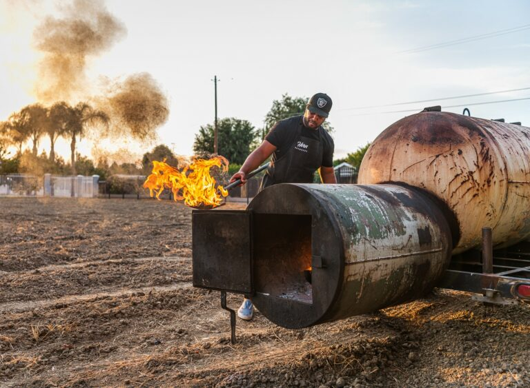 Pitmaster Matt Horn Facing Smoker with Flames