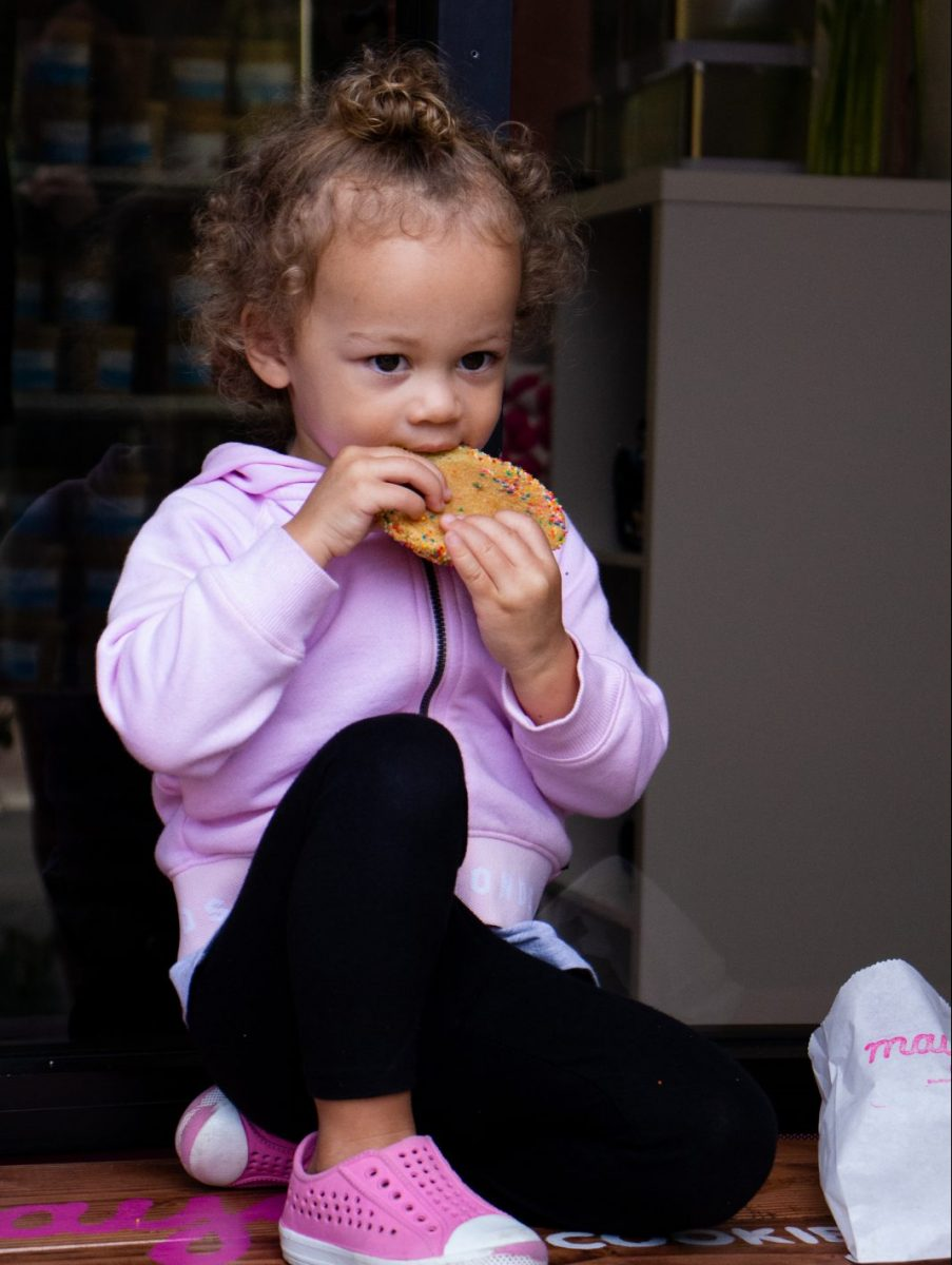 Little girl eating a cookie from Maya's Cookies