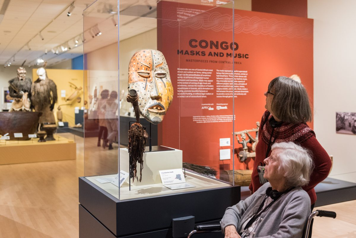Museum attendees looking at mask