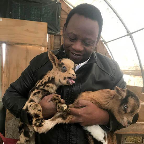 Muhidin Libah holding goats on the farm