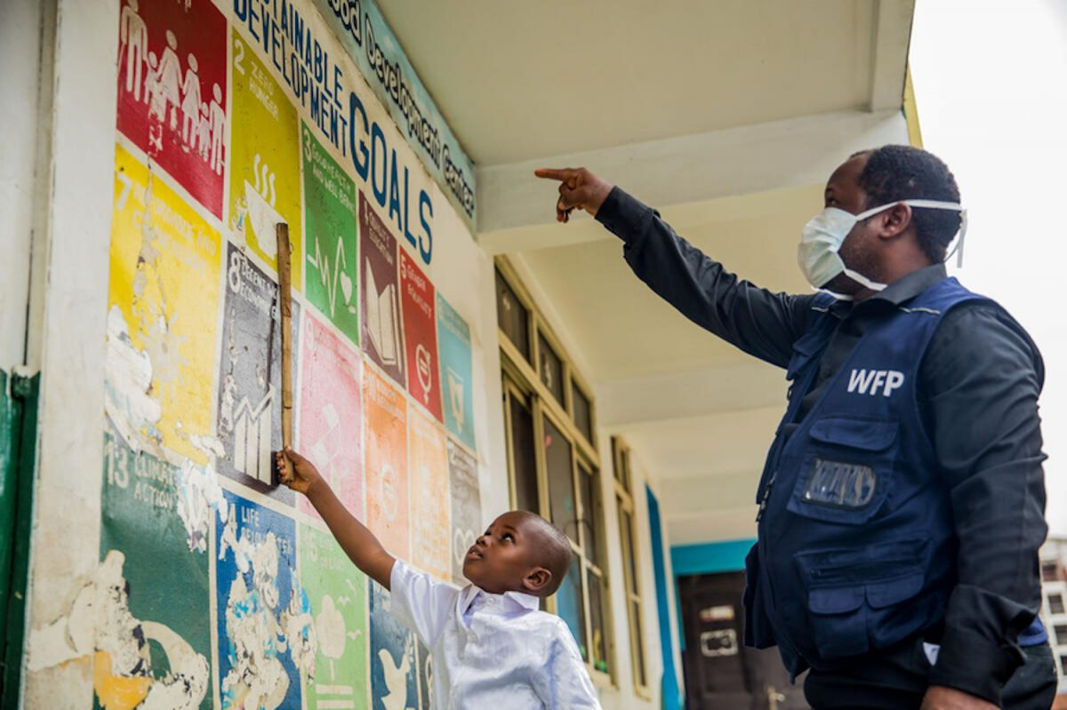 World Food Programme (WFP) staff member teaches David, a student, about the Sustainable Development Goals at a distribution centre for the National Home Grown School Feeding Programme supported by WFP in Nigeria.